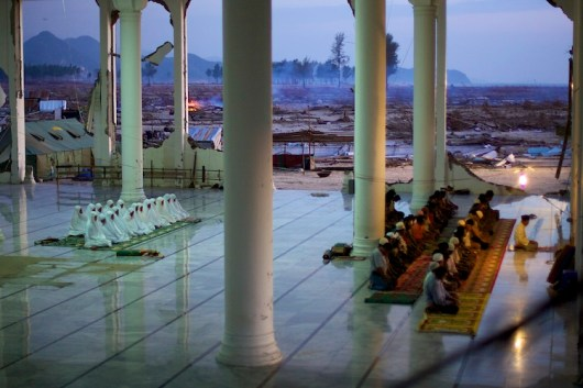 The surviving residents of a village pray in a mosque, the only standing structure of a city completely decimated by the 2004 Indian Ocean tsunami which hit Aceh, Indonesia.
