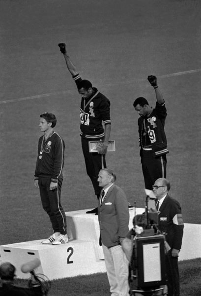 """FILE - In this Oct. 16, 1968 file photo, United States athletes Tommie Smith, top center, and John Carlos, top right, extend their gloved fists skyward during the playing of the """"Star-Spangled Banner"""" after Smith received the gold and Carlos the bronze for the 200-meter run at the Summer Olympic Games in Mexico City. Australia's silver medalist Peter Norman is at left. When Tommie Smith bowed his head and thrust a black-gloved fist toward the sky from the top of the Olympic podium 45 years ago, he was making a personal statement about human rights. With questions swirling over an anti-gay law in Russia, which will host the Winter Games in Sochi in February, today's athletes face a similar choice, Smith told The Associated Press Sunday, Sept. 8, 2013, at a track and field meet in Rieti, Italy. (AP Photo/File)/NY152/717491874698/AN OCT. 16, 1968, B&W FILE PHOTO; /1309091753"""