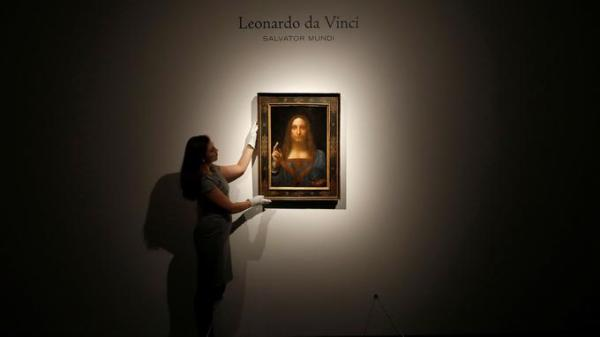 "Members of Christie's staff pose for pictures next to Leonardo da Vinci's ""Salvator Mundi"" painting which will be auctioned by Christie's in New York in November, in London, Britain October 24, 2017. REUTERS/Peter Nicholls NO RESALES. NO ARCHIVES - RC110F6E4140"