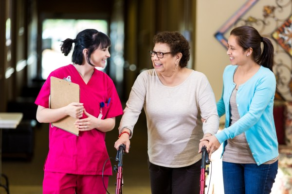 Hispanic senior woman and her granddaughter listen to a nurse in assisted living facility as she gives them a tour of the facility. the women talk with one another as they walk through the building. The senior woman is using a walker and her granddaughter is helping her.