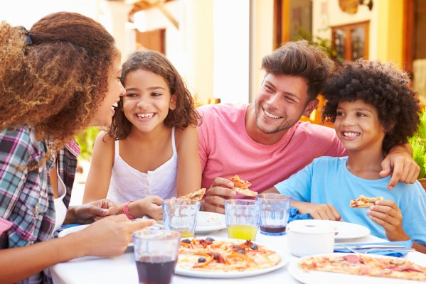 Family Eating Meal At Outdoor Restaurant Together, Smiling