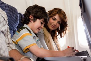 Woman looking at boy next to her on airplane.
