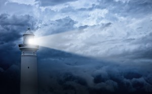 Lighthouse shines its light at against an angry-looking sky.