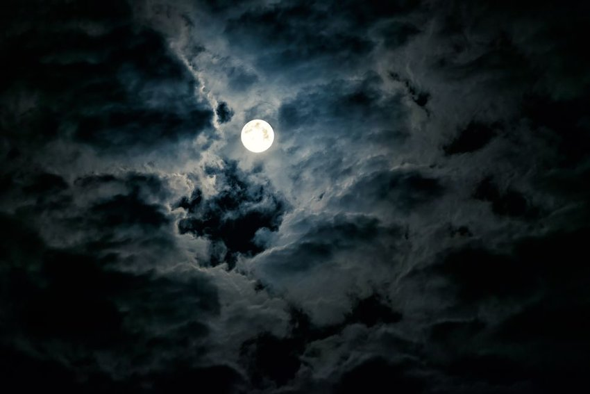 Sky view of large full moon illuminating scattered clouds at night