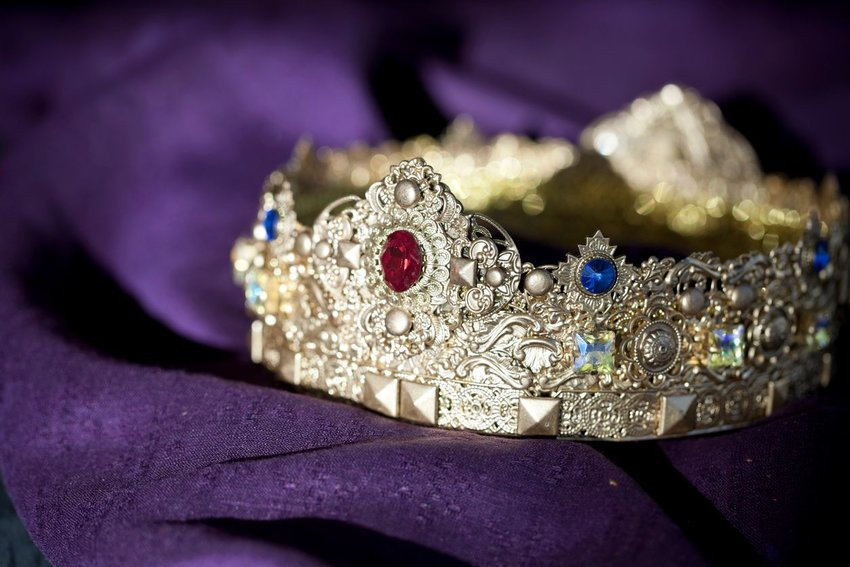 Crown with jewels laying on a purple background