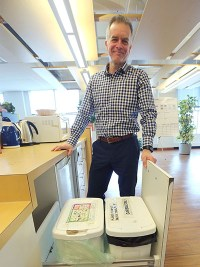 Dennis Cunningham, Manager, Environmental Sustainability at Assiniboine Credit Union, shows off composting instruction sheets and a bin at Assiniboine Credit Union's 200 Main St. offices. Photo by Jason Halstead