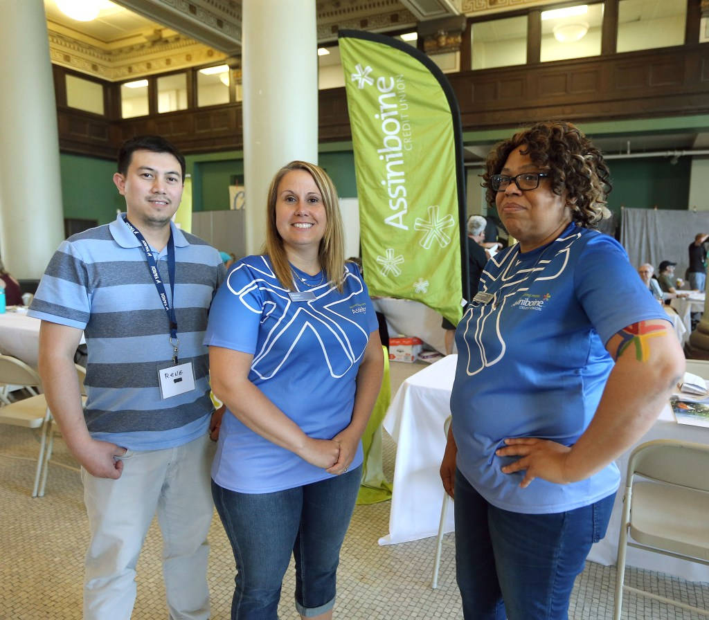 Date: May 26, 2018 L-R: Assiniboine Credit Union participants Renato Sangalang (inbound communication centre representative), Kelly Guerra (West Broadway branch manager) and Michelle Williams (financial advisor) at the Gizhe Waa Ti-Sii-Win Service Delivery Expo organized by End Homelessness Winnipeg on Saturday, May 26, 2018 at the Neeginan Centre on Higgins Avenue in Winnipeg. Photo by Jason Halstead