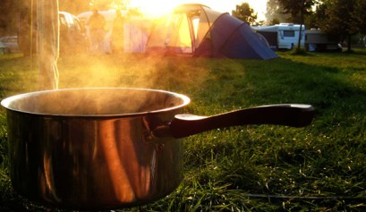 rv camping for less, rv camping, camping, picture of a pot with steam coming out of it with rvs and tents in the background