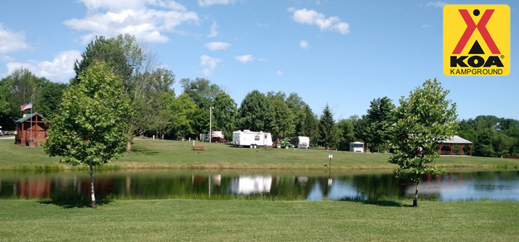 homerville koa, picture of the fishing lake at homerville koa with rvs in the background and the koa logo in the top left, koa
