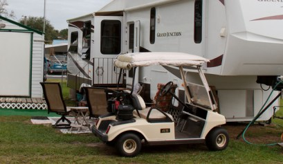 7 tips for full time rv living, picture of a fifth wheel rv and a golf cart in the foreground