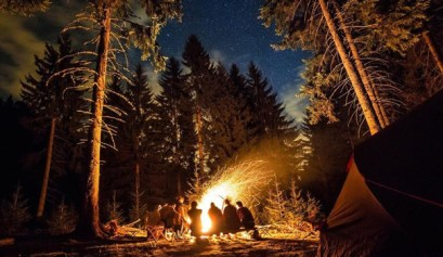 great camping checklist, picture of people sitting at a camp fire during a starry night