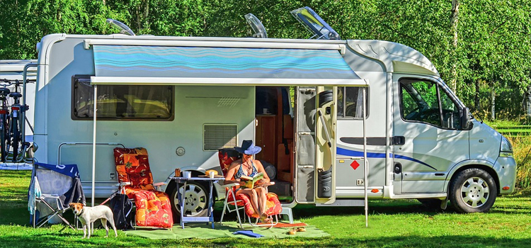 full time rv tips, picture of a motorhome and rver sitting under her awning while enjoying nature, full time rv tips to save money and see the sites