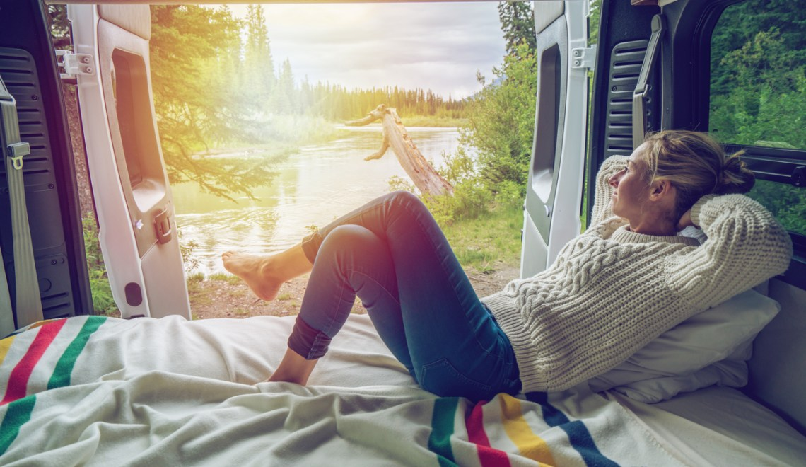 rv life picture with a women laying in the back of a rv looking out onto a lake and sunset