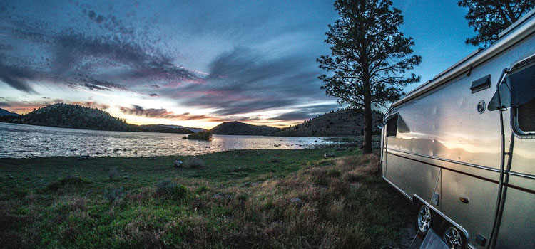 tips on how to go rving alone, rving alone, picture of a airstream travel trailer sitting in an open field with a gorgeous sky