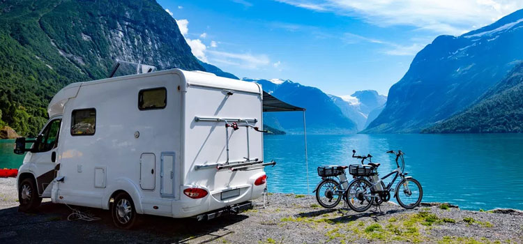 picture of a motorhome with 2 bikes behind it sitting in front of a blue lake with mountains in the background for expert rv camping