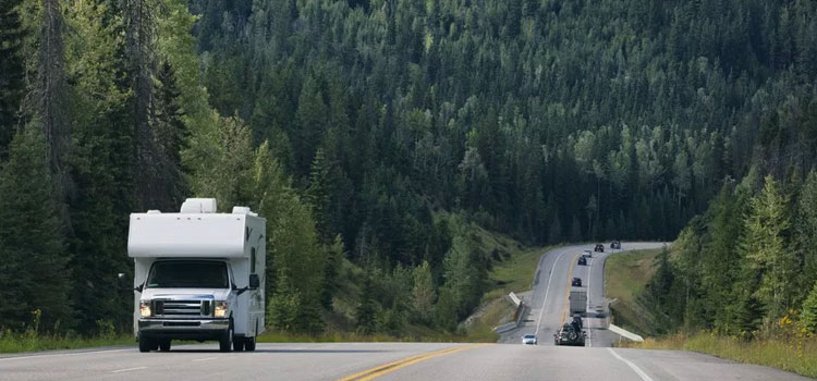 picture of a motorhome driving down the road with pine trees in the background for rv travel safety