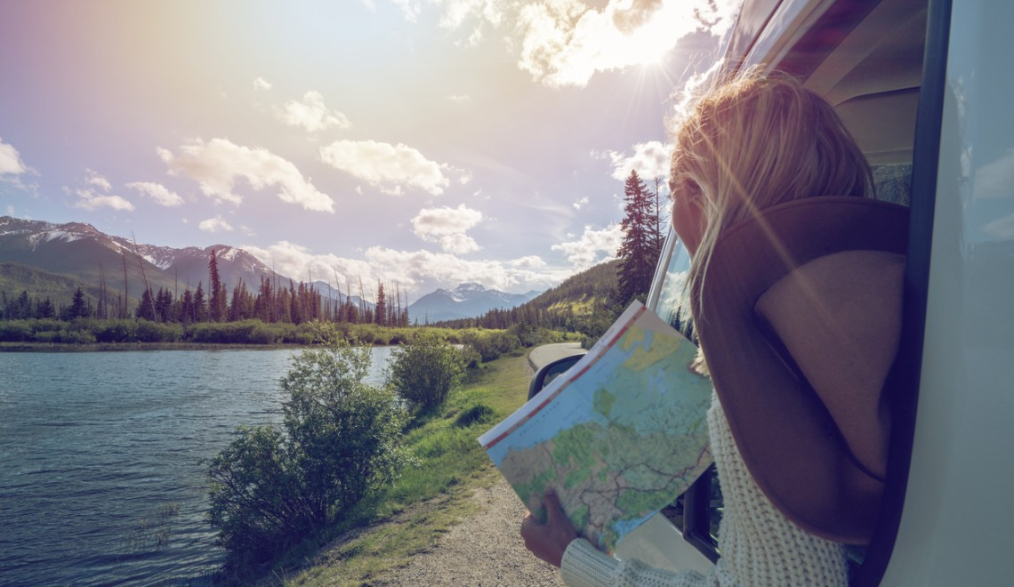 young woman looking at map inside rv with spring mountain lake background