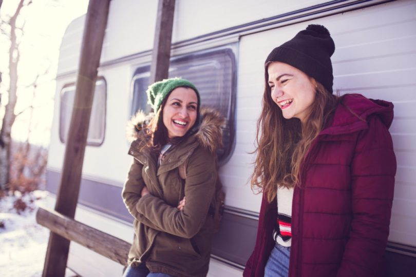 Girls Standing Near RV at Park On Cold Winter Day, Laughing Together