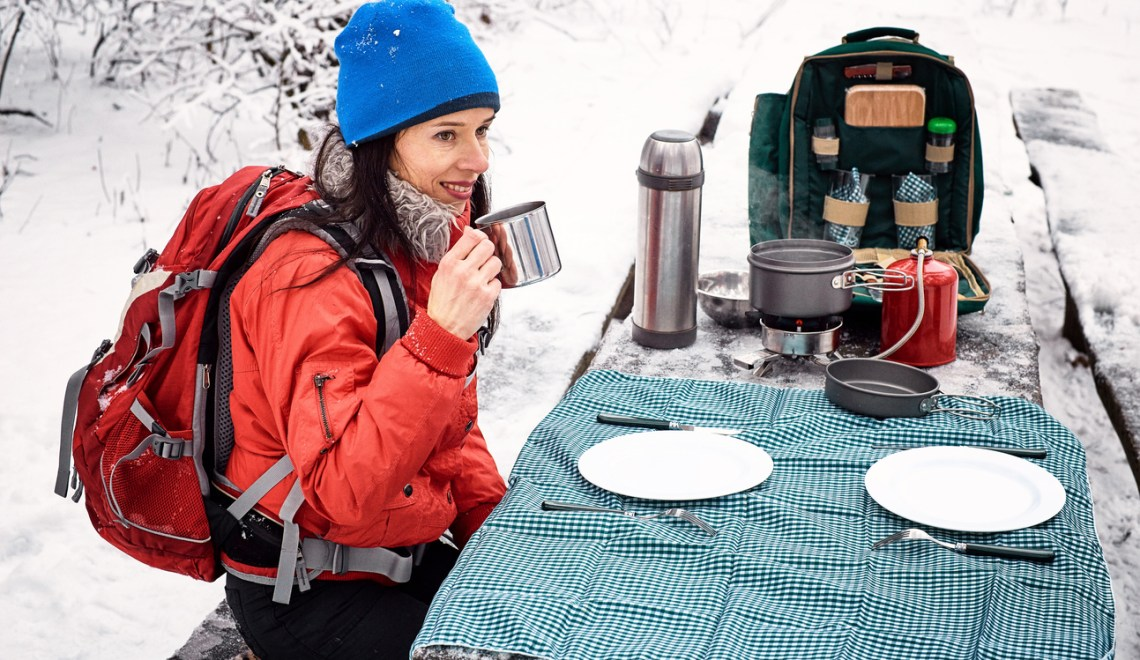 Camping at a table in a winter forest with a backpack, thermos and a burner.