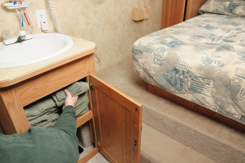 Person packing towels in rv bathroom and bedroom cabinet