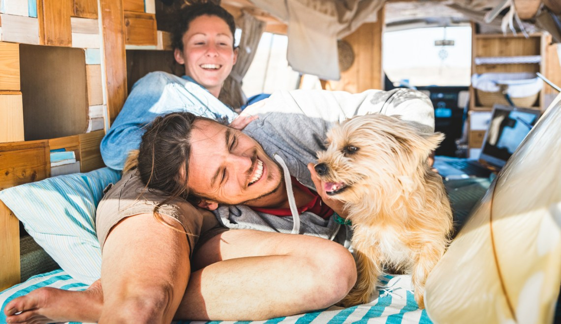 Hippie couple with funny dog traveling together on an RV trip - Life inspiration concept with indie people on adventure camping with dogs