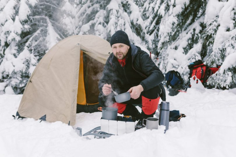 Winter camping recipes: A man is cooking food near his tent in the winter forest