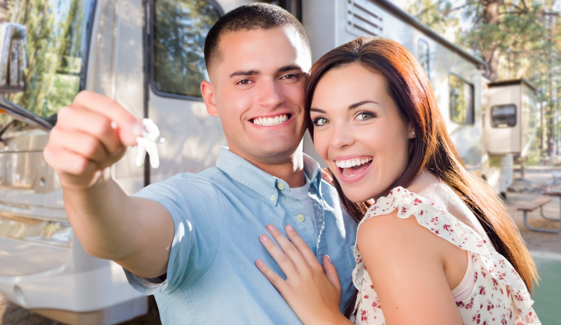 Young Military Couple Holding Keys In Front of New RV. Full-Time RV Living concept