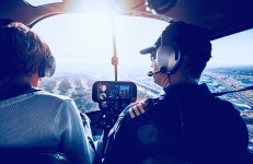 Inside view of a helicopter in flight with man and woman pilots flying a helicopter on a sunny day.