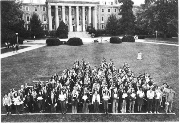Fotografia de um grupo de estudantes organizados por altura, mostrando um histograma bimodal.