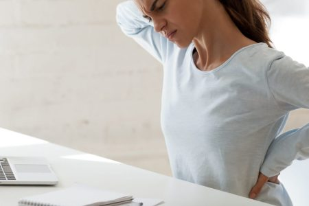 woman suffering from back pain in home office chair