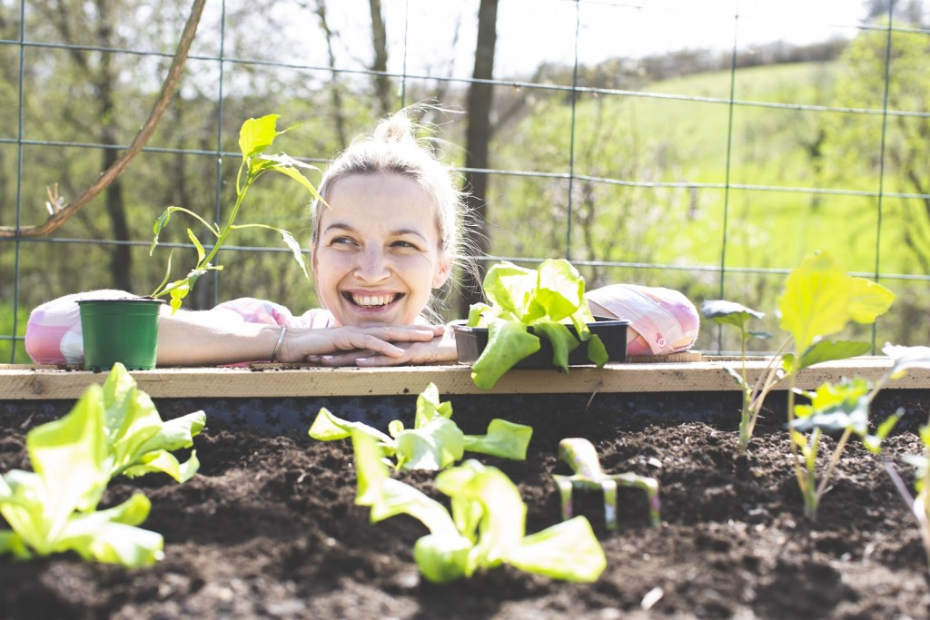 Woman smiling while looking at her raised garden bed