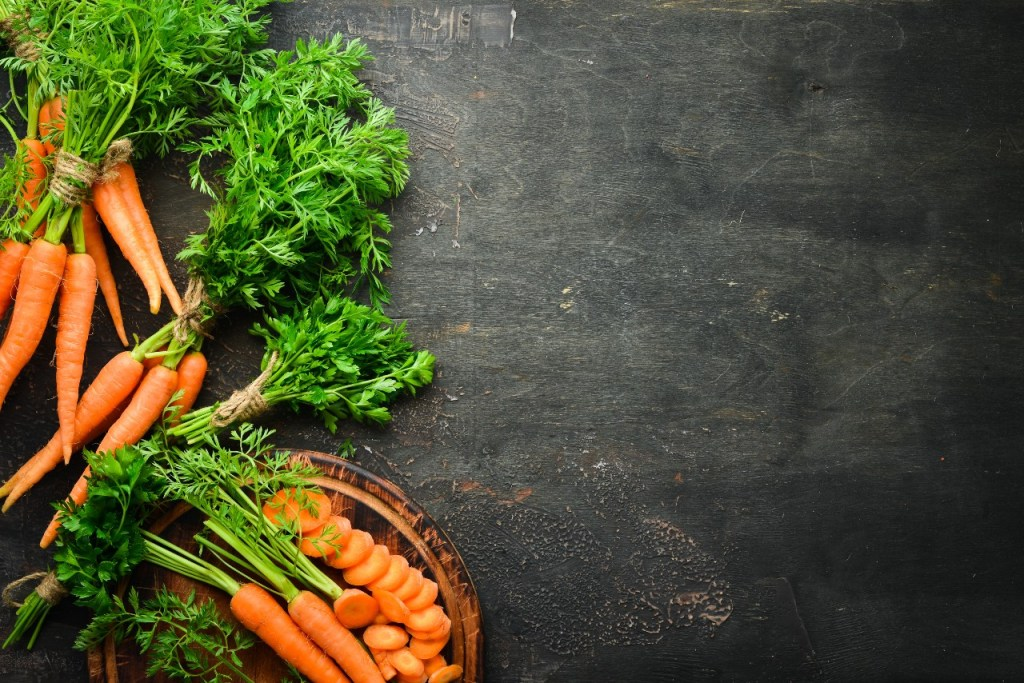 fastest growing vegetables: Carrots against a black wooden background