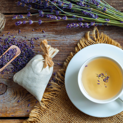 how to grow lavender: A cup of lavender tea on a wooden table surrounded by fresh lavender