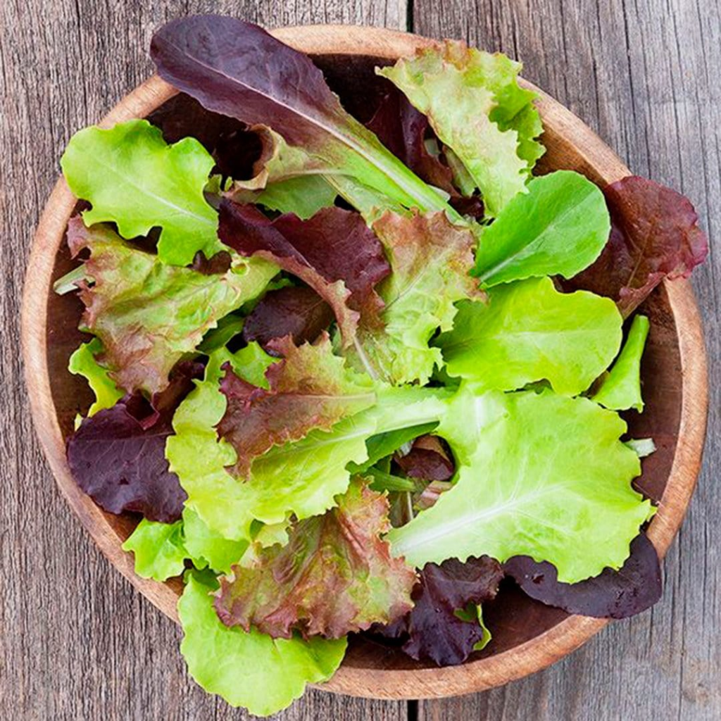 Lettuce in a wooden bowl on top of a wooden table