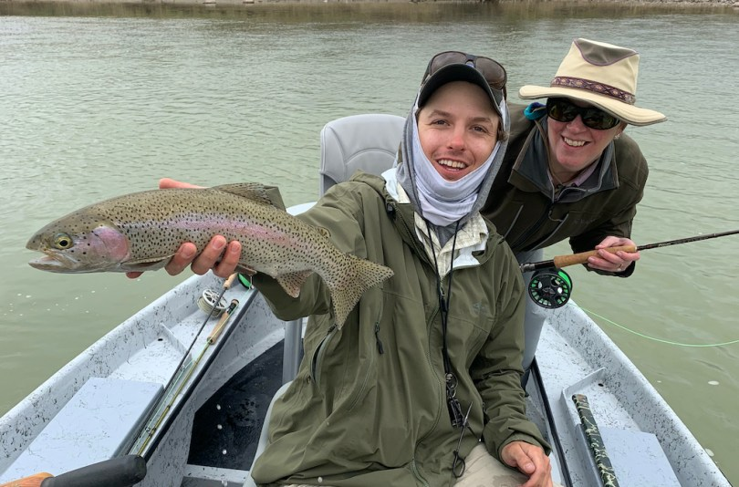 An angler, a guide, and a trout