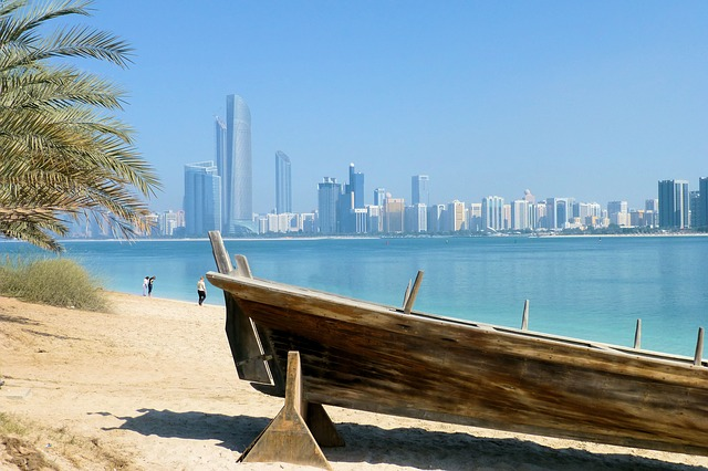 A wooden boat on the shore of a harbour looking out to the water and the skyline of Dubai