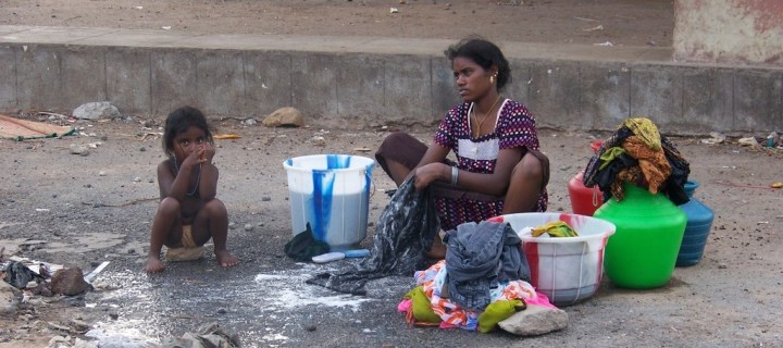 A woman and her daughter wash their clothes in washtubs on the street - Bel