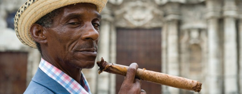 A man with a hat smoking a cigar in Cuba