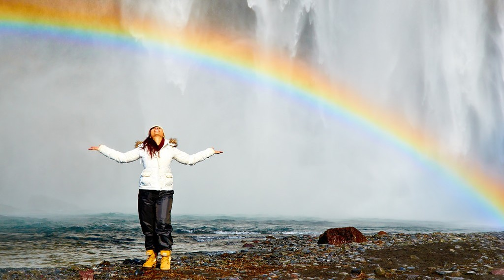 A woman smiling under a rainbow in happiness - picture by Moyan Brenn on Flickr