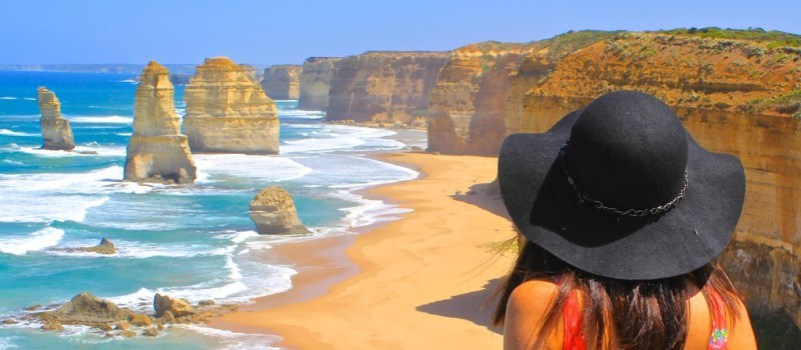 Woman wearing a hat looking at the cliffs and the sea