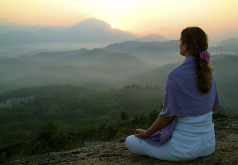 A woman meditating on a mountain top