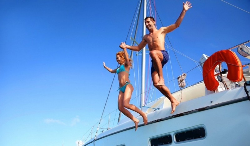 A couple jumping from a Yacht in Greece