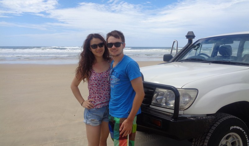 A couple smiling in front of a FWD on Frasier Island, Australia