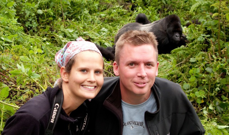Couple smiling in front a gorillas in the wild