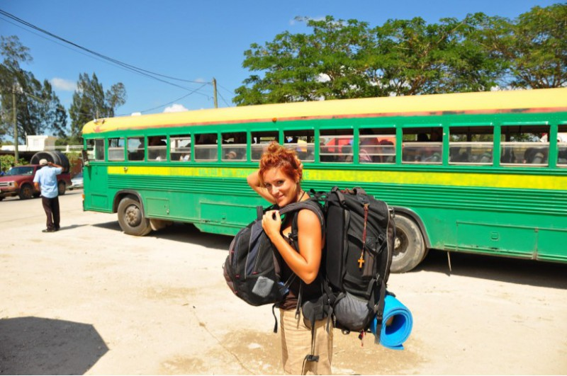 solo travel tips 1: smile - young female solo traveller smiling and posing in front of a colourful bus