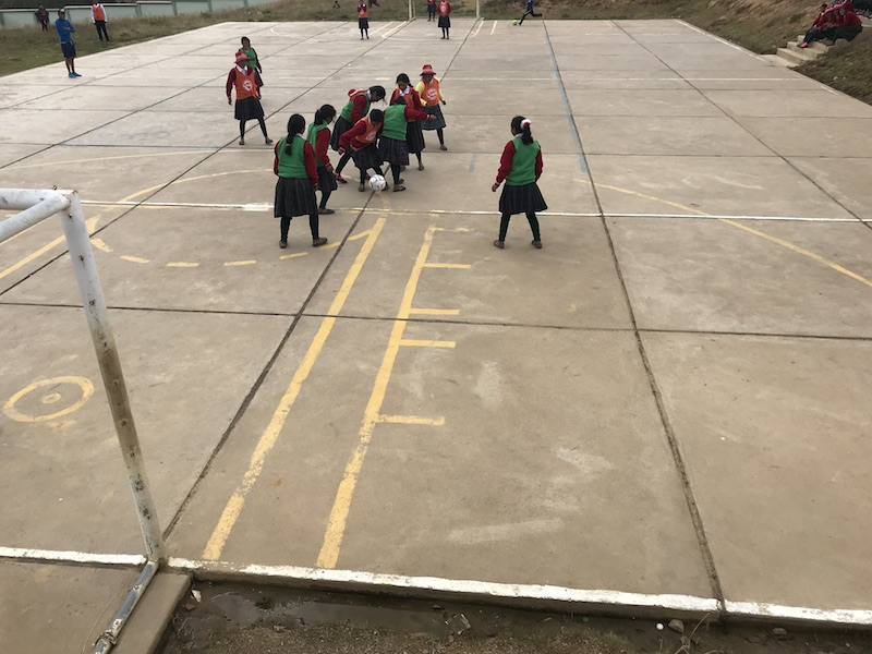 Children play on a concrete football field in Peru