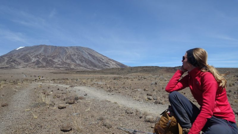 Sitting woman with blond hair looks along a trek to Mount Kilimanjaro