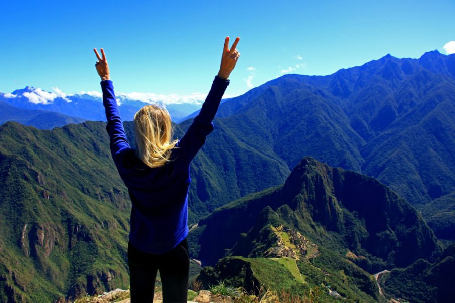 Woman stands in triumph overlooking Machu Picchu