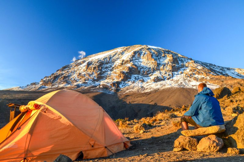 Man sits next to his tent at sunrise on Mount Kilimanjaro