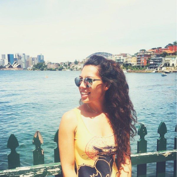 Woman with long curly hair and sun glasses smiles long-distance friendship